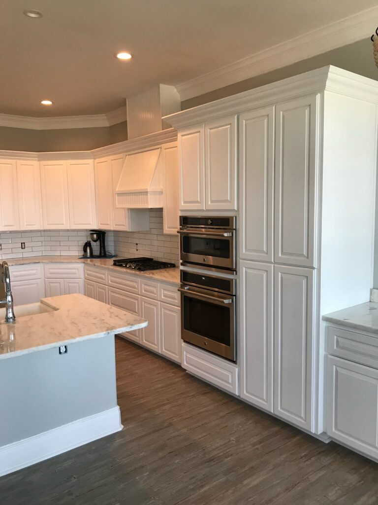 Kitchen with double ovens white cabinets